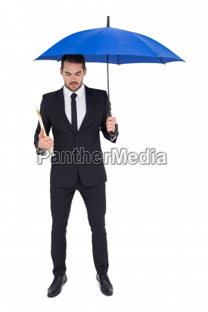 businessman holding file under a blue