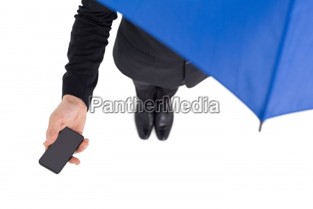businessman under umbrella holding mobile phone