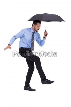 focused businessman holding umbrella and balancing
