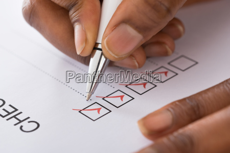 persons hand marking on checklist form
