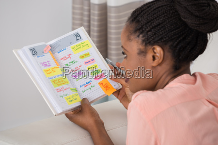 young woman writing schedule in diary