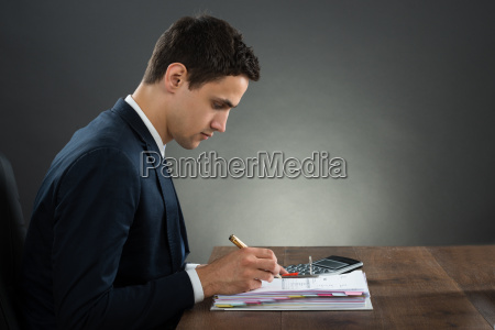businessman examining invoice at desk