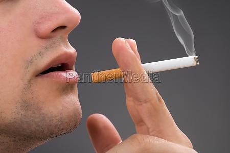 man rauchen vor grauem hintergrund
