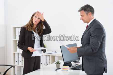 businessman giving document to stressed businesswoman