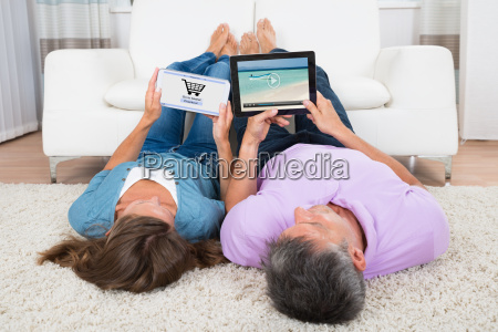 woman shopping online while man watching