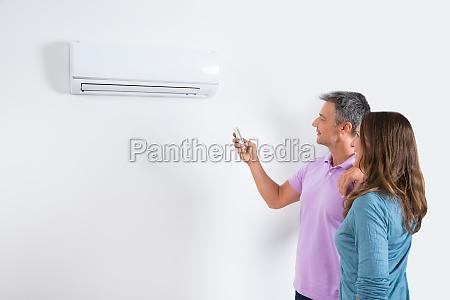 couple adjusting temperature of air conditioner
