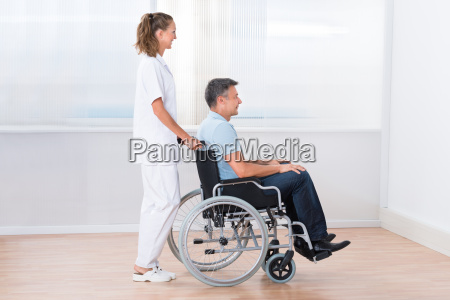 doctor pushing disabled patient on the