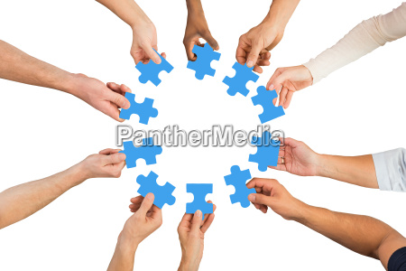 creative business people holding blue jigsaw