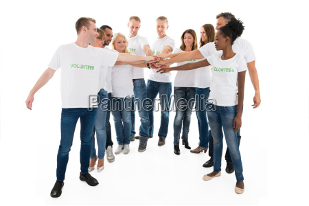 multiethnic volunteers stacking hands against white