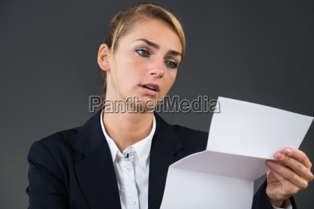 shocked young businesswoman reading letter at