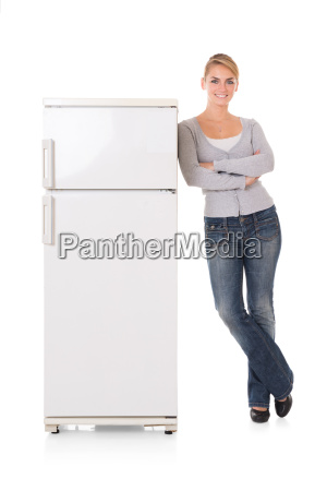 woman leaning on refrigerator over white