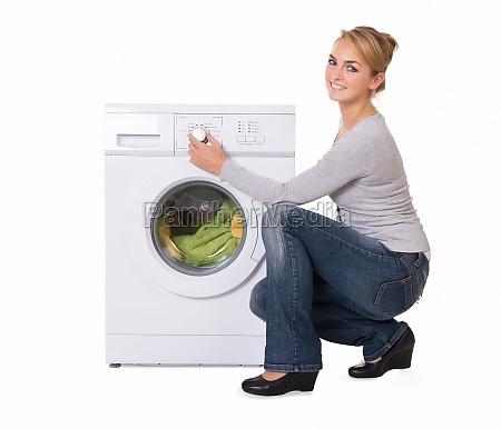 woman crouching while using washing machine