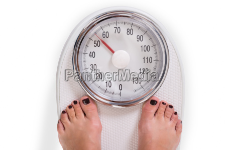 womans legs on weighing scale over
