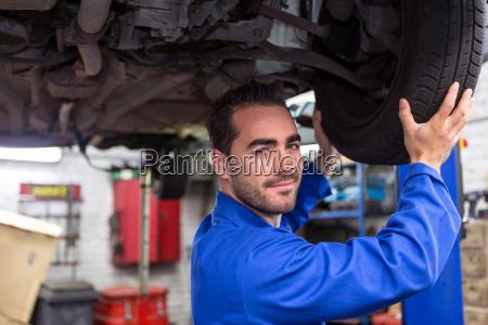 junge attraktive mechaniker auf einem auto