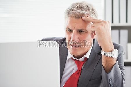 verwirrter geschaeftsmann der seinen laptop betrachtet