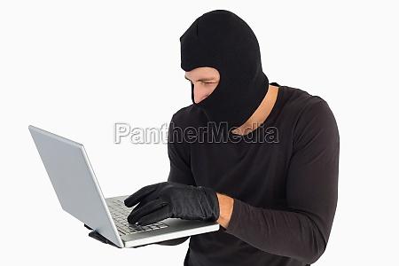 focused burglar standing holding laptop