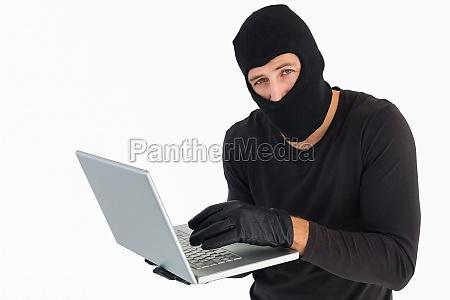 burglar standing holding laptop while looking