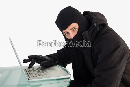 burglar using laptop while looking at