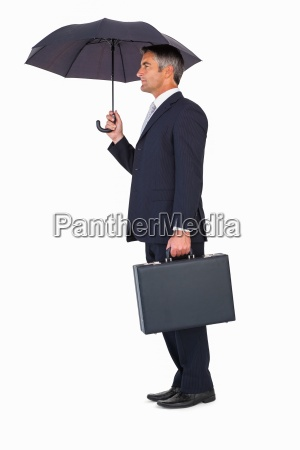 businessman holding briefcase under umbrella