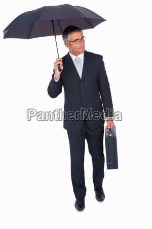 businessman holding briefcase and standing under