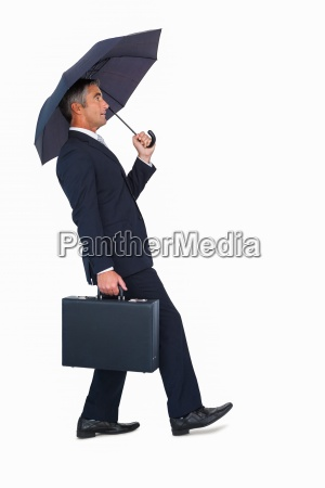 businessman walking and holding briefcase under