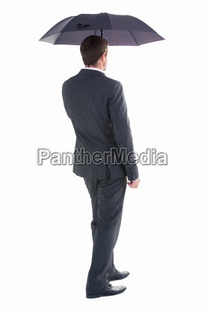 businessman walking and holding umbrella