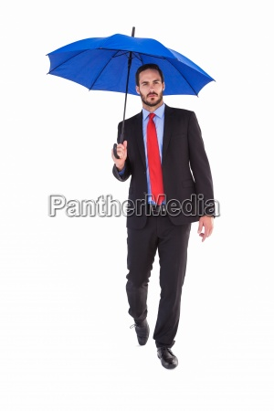 unsmiling businessman holding an umbrella