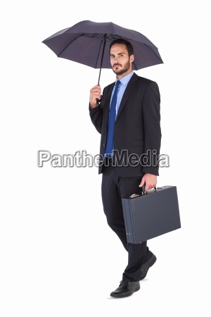 businessman in suit holding umbrella and