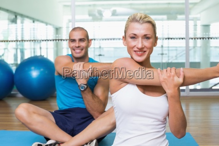couple stretching hands in yoga class