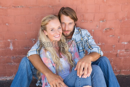 attractive couple sitting on ground
