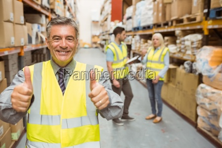 manager smiling at camera showing thumbs