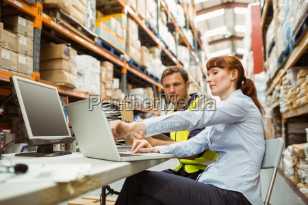 warehouse worker and manager looking at