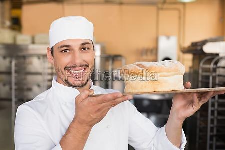 smiling baker showing loaf of bread