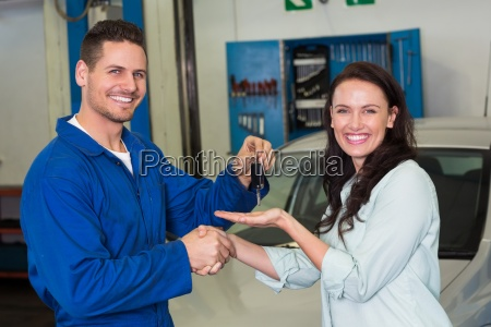 mechanic and customer smiling at camera
