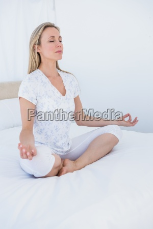 blonde woman sitting in lotus pose
