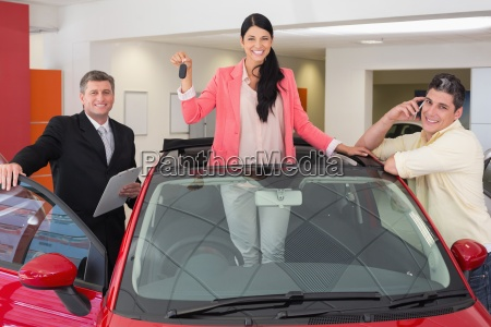 woman standing in red cabriolet while
