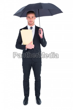 businessman sheltering under umbrella holding file