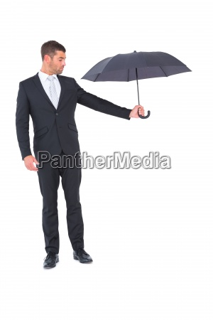 businessman holding black umbrella beside him