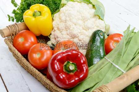 basket of seasonal vegetables on white