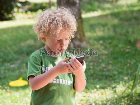 little blond and curly boy playing
