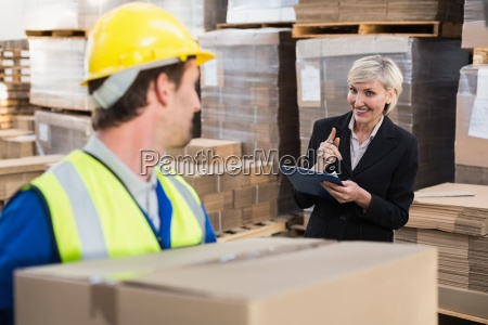 warehouse worker holding box with manager