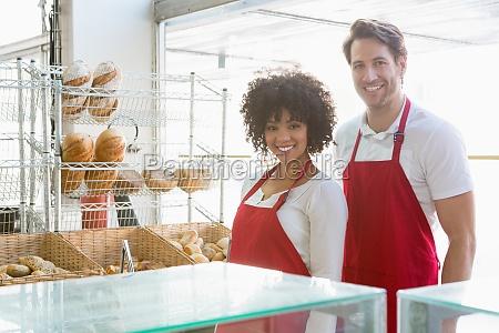portrait eines gluecklichen mitarbeitern stehend hinter