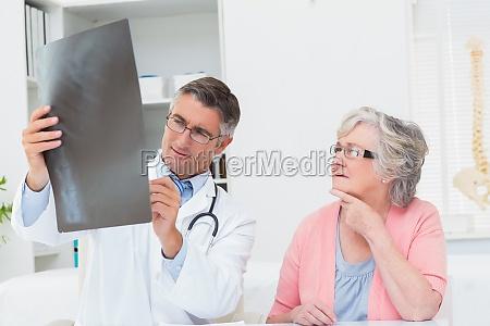 doctor explaining x ray to female