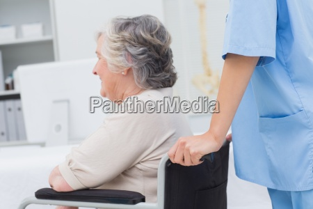 nurse pushing senior patient in wheelchair