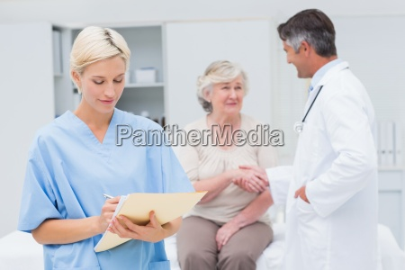 female nurse making reports while doctor