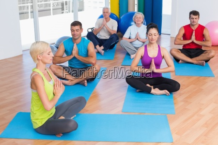 female instructor with class meditating at