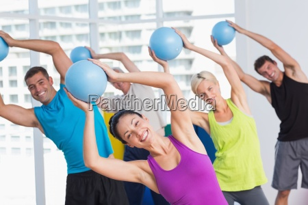 instructor with class exercising with fitness