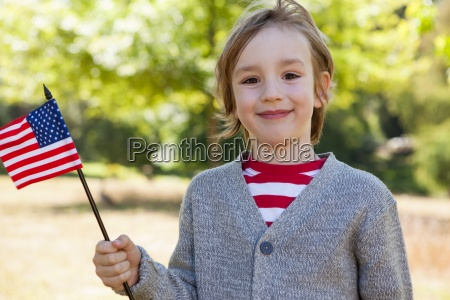 cute little boy waving american flag