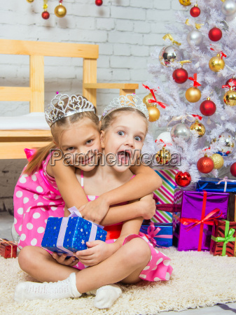 girl hugging another girl sitting on