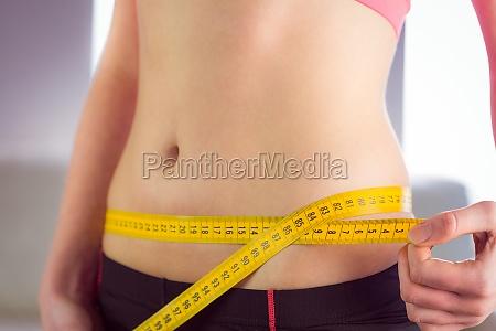 slim woman measuring waist with tape